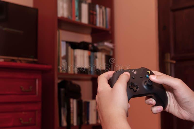 Caucasian pojke som spelar på Xbox en videospel arkivbild