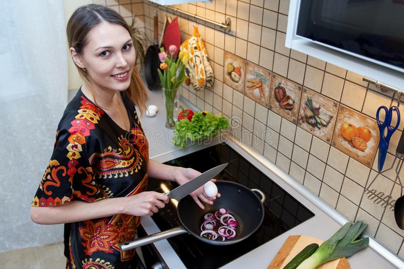 Caucasian pretty girl with a smile does the cooking in the kitchen. She cooks scrambled eggs in a frying pan, dressed in royalty free stock photo