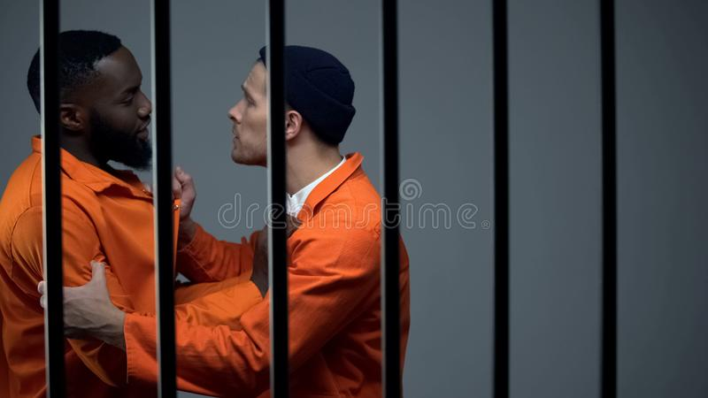 Caucasian prisoner fighting with black inmate, discrimination, jail overcrowding stock images