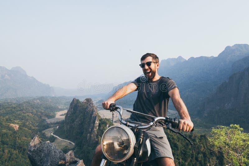 Caucasian ridningmotorcykel för ung man överst av bergen i Vang Vieng, Laos royaltyfri fotografi
