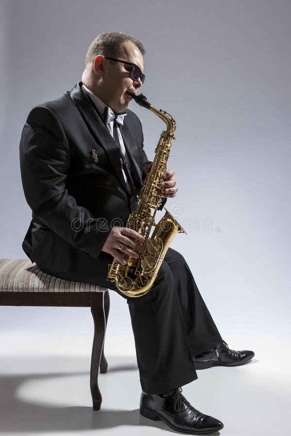 Caucasian Saxophone Player in Sunglasses Playing the Saxophone While Sitting on Chair in Studio Environment. Music Concepts. Portrait of Mature Relaxed and stock photo