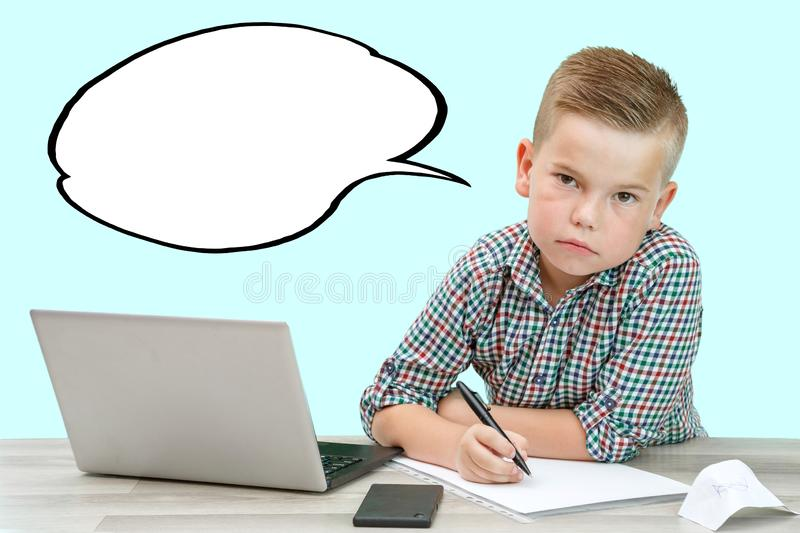 Caucasian school-age boy in a plaid shirt on an  background with a laptop and a phone records thoughts in a piece of paper.  royalty free stock photo