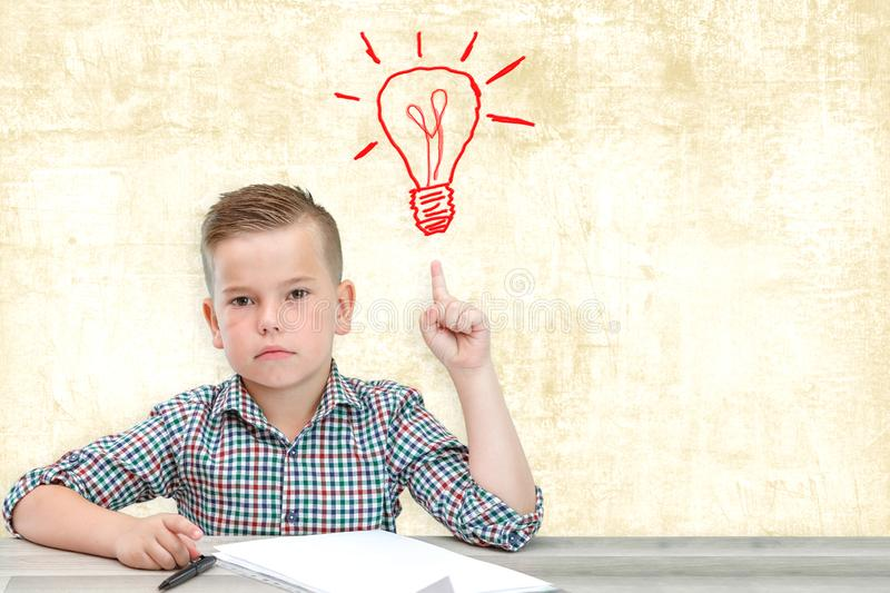 Caucasian school-age boy in a plaid shirt on an  background writes thoughts in a sheet. Caucasian school-age boy in a plaid shirt on an  background writes stock images
