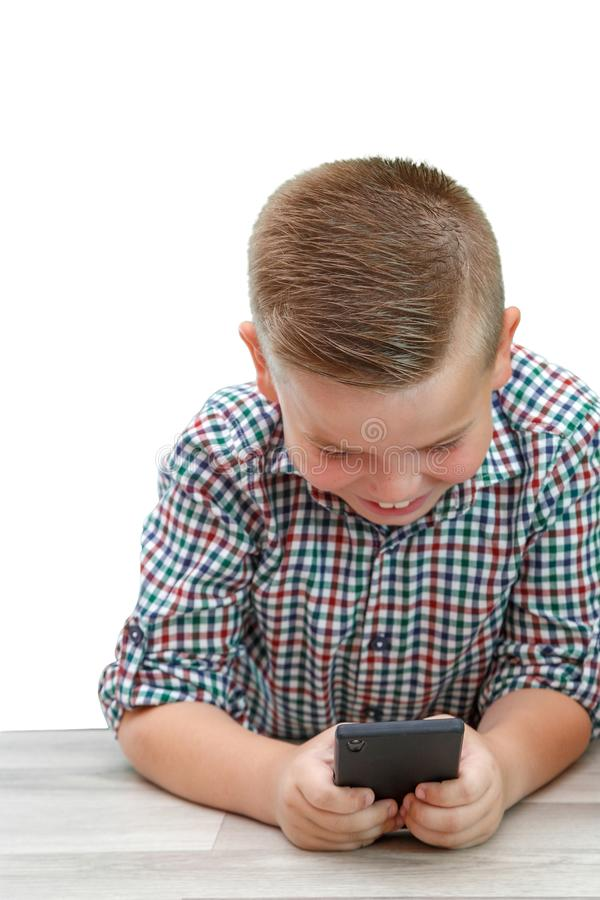 Caucasian school-age boy in plaid shirt on light isolated background playing games on phone. modern children, their interests.  stock image