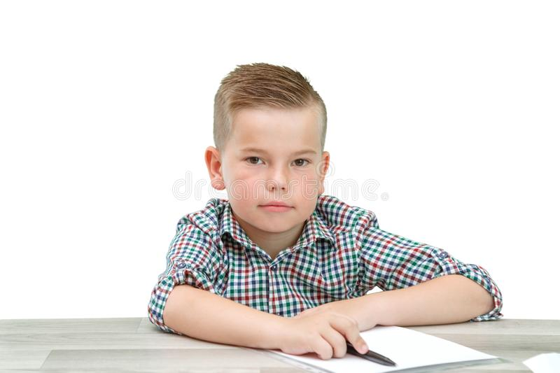 Caucasian school-age boy in a plaid shirt sitting at the table and writing in a piece of paper . there is also a laptop and a. Phone on the table royalty free stock images