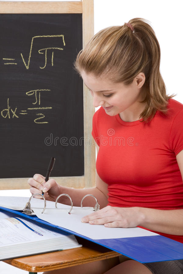 Caucasian schoolgirl by desk studying math exam stock images