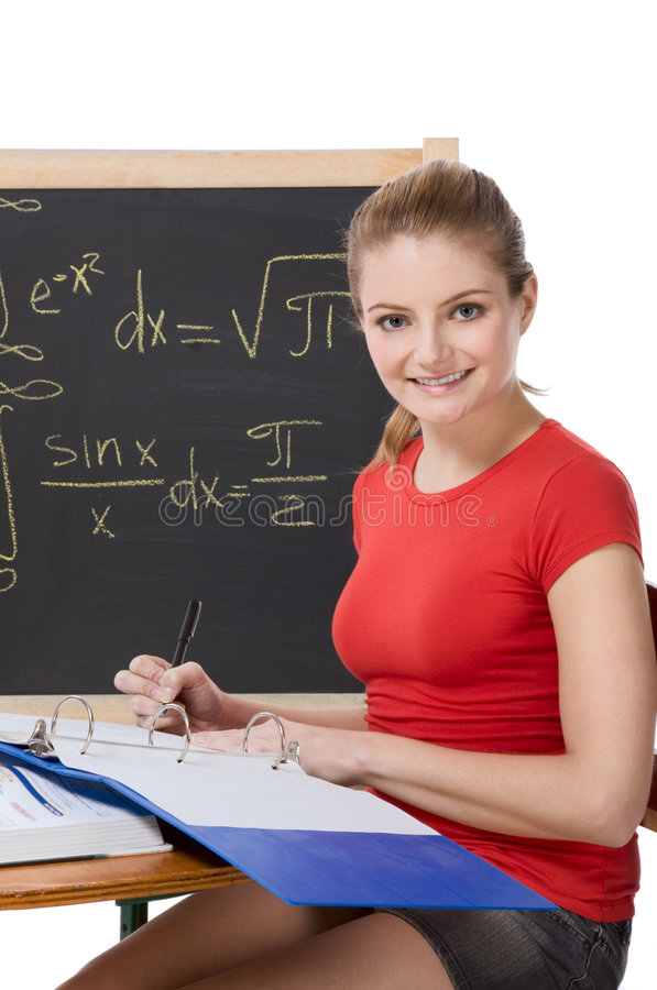 Caucasian schoolgirl by desk studying math exam royalty free stock images