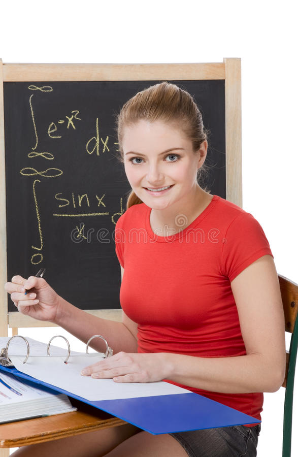 Caucasian schoolgirl by desk studying math exam royalty free stock image