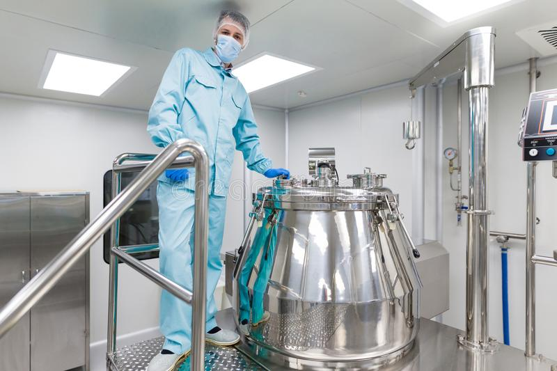 Scientist stand near big metal barrel. Caucasian scientist in blue lab suit and gloves stand near bid steel tank with cap, look at camera, hand on handrail royalty free stock images