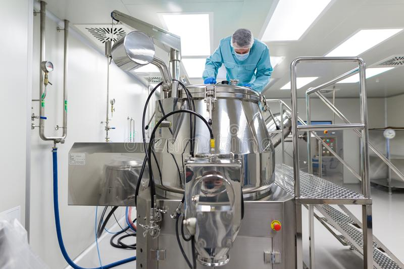 Scientist look in steel tank in laboratory. Caucasian scientist in blue lab suit and gloves stand on platform and look in the chromed tank, clean laboratory stock photo