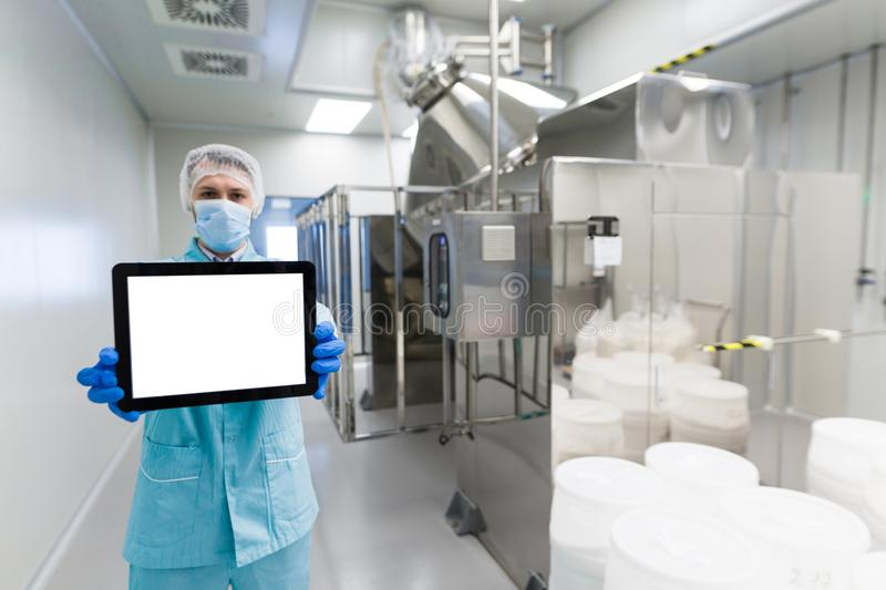 Scientist show empty tablet near steel machine. Caucasian scientist in blue lab uniform and gloves show empty tablet to camera near steel machine with tanks stock photos