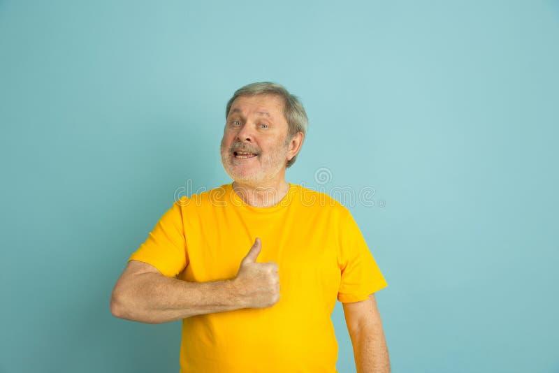 Caucasian senior man`s portrait isolated on blue studio background royalty free stock photography