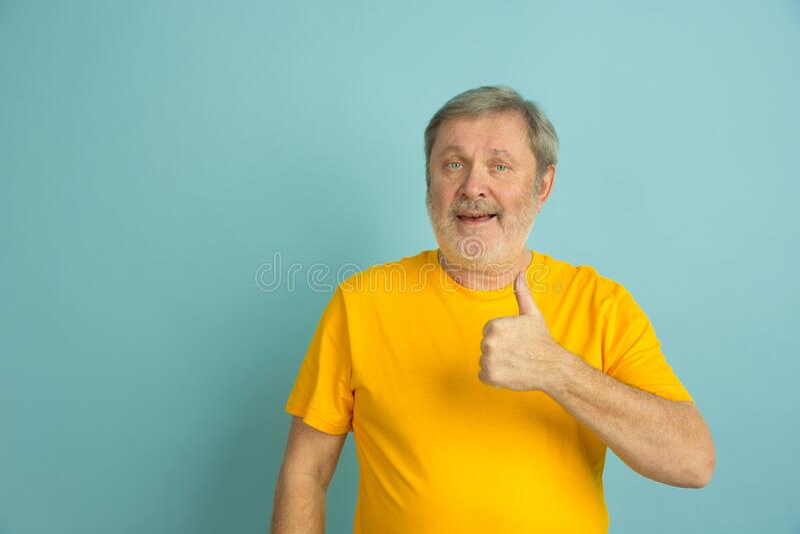 Caucasian senior man`s portrait isolated on blue studio background royalty free stock image