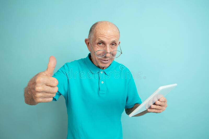 Caucasian senior man`s portrait isolated on blue studio background stock images