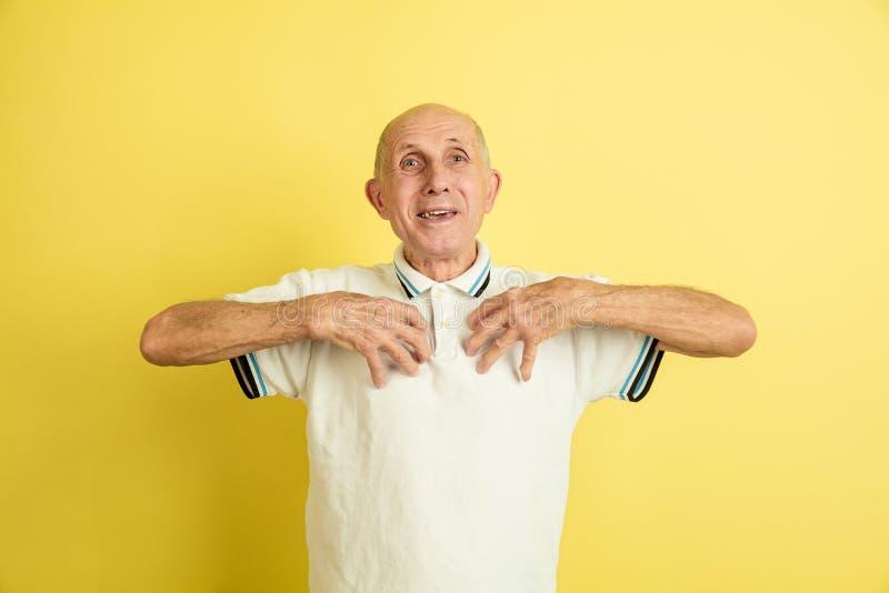 Caucasian senior man`s portrait isolated on yellow studio background royalty free stock photo