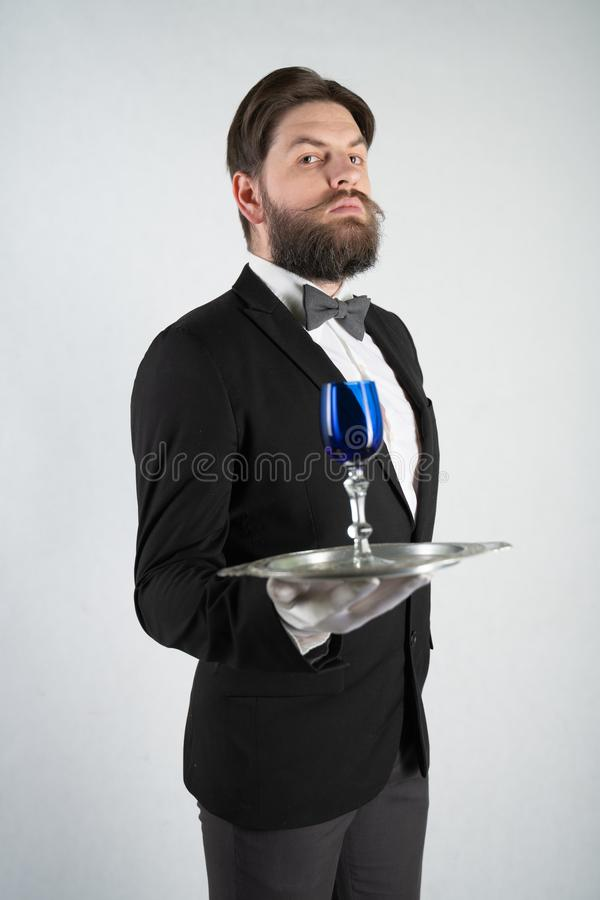 Caucasian servant with a beard in a formal business suit stands with a steel tray in his hand and a glass of wine on a white solid stock photography