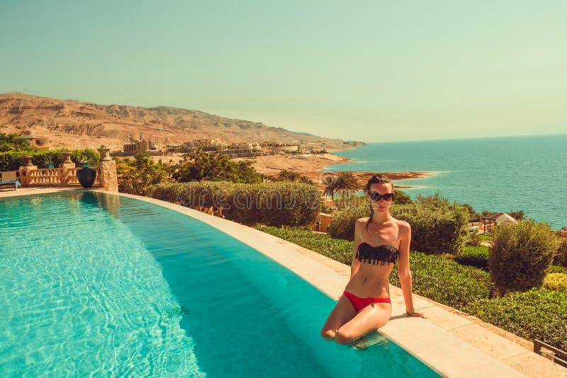 Caucasian sexig mager modell med den tunna midjan som kopplar av i lyxig oändlighetspöl Den unga kvinnan vilar i brunnsortsemeste royaltyfri foto