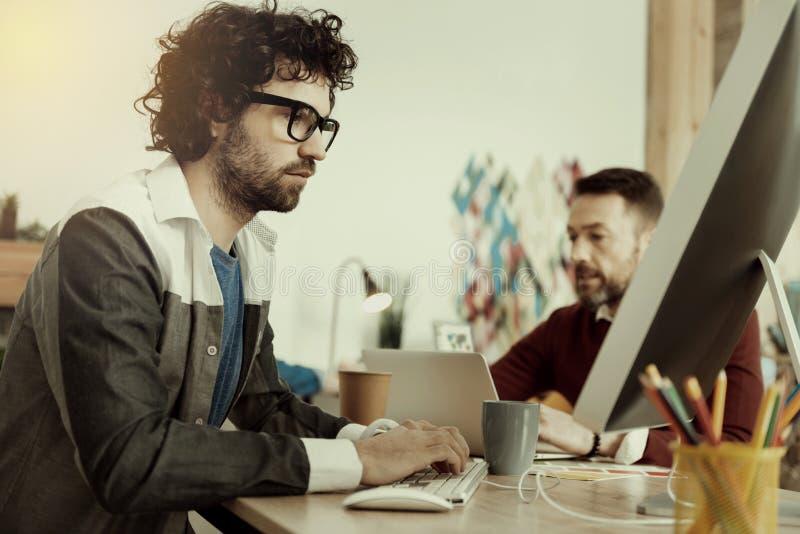 Caucasian skäggig specialist i exponeringsglas som ser allvarliga arkivfoto