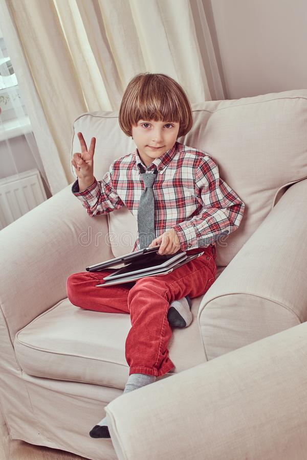 Caucasian skolpojke som bär en rutig skjorta med bandet som visar fredtecknet och rymmer en minnestavla, medan sitta på en soffa arkivfoto