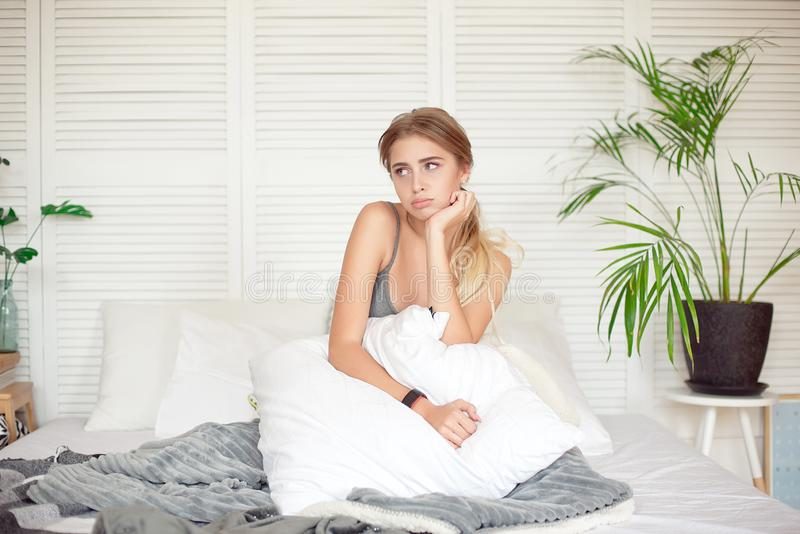 Caucasian sleepy young attractive woman feeling drowsy after woke up, sits on the bed having bad mood after sleepless stock photos