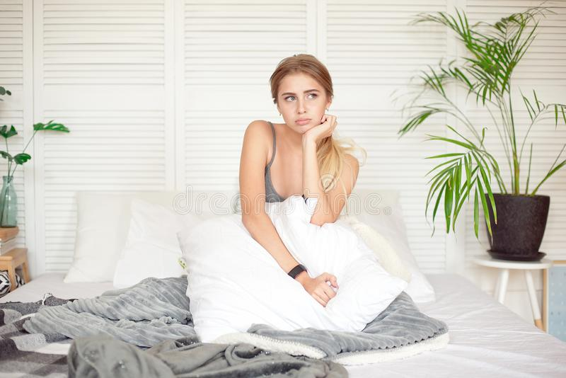 Caucasian sleepy young attractive woman feeling drowsy after woke up, sits on the bed having bad mood after sleepless royalty free stock photography