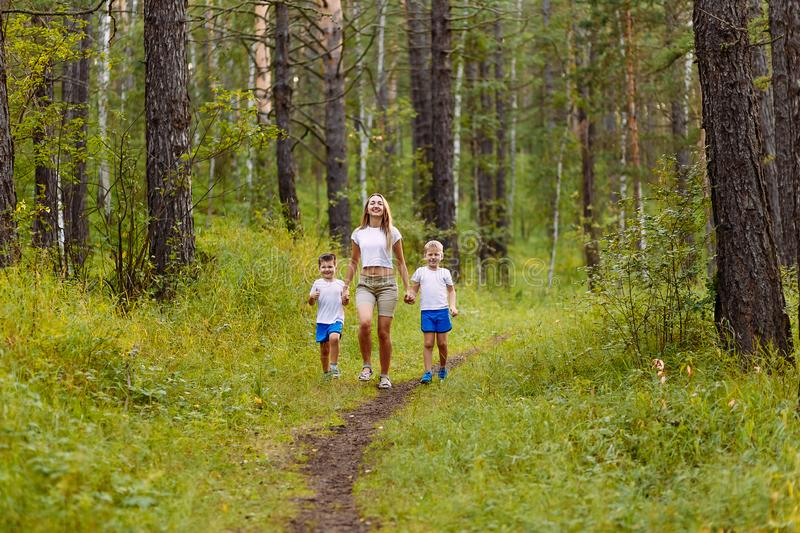 A Caucasian slender smiling woman and two pre-school children in white t-shirts run along the path, holding hands in the summer. Outdoors . Mother and children royalty free stock image