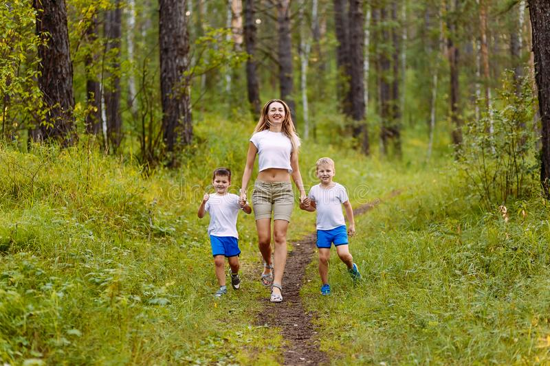 A Caucasian slender smiling woman and two cheerful preschoolers children in white t-shirts run along the path, holding hands in. A Caucasian slender smiling royalty free stock photo