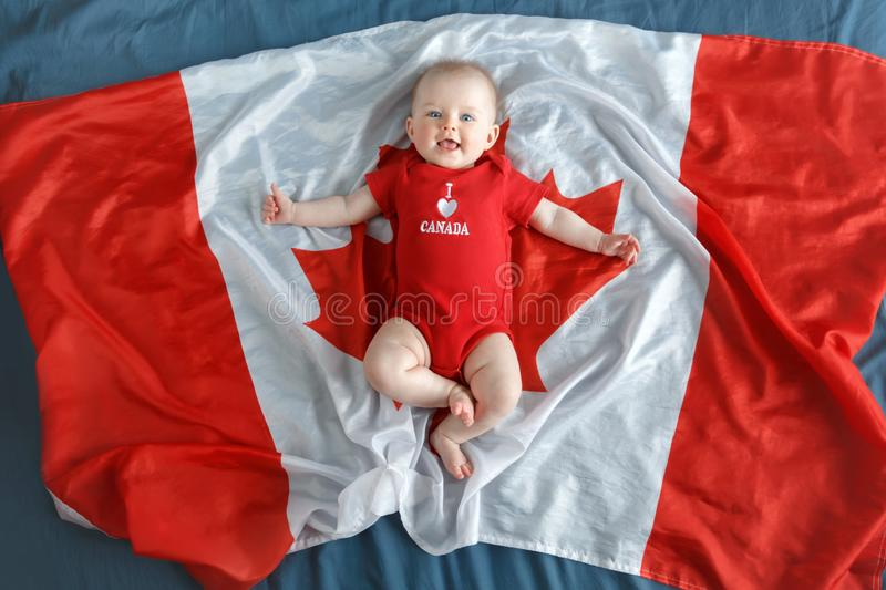Caucasian smiling baby boy girl with blue eyes lying on large Canadian flag with red maple leaf stock image