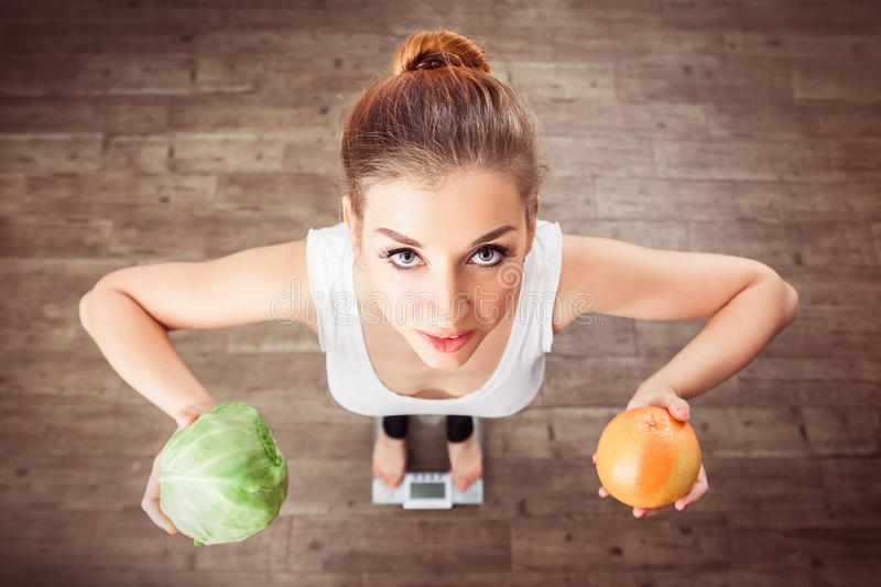 Caucasian smiling girl stands on scales and holding a cabbage and grapefruit in her raised hands stock photos
