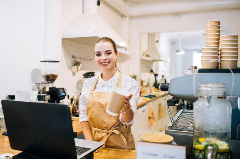 Caucasian smiling woman barista at the counter, suggesting a coffee cup. stock image