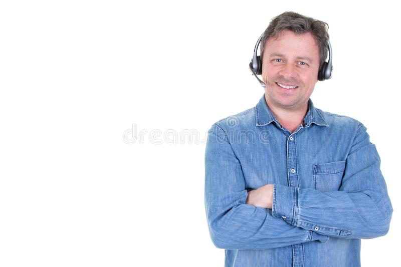 Caucasian stilig man i jeansskjortaanseende med hörlurar med mikrofonanställd av helpdesk- eller appellmittbegreppet som isoleras royaltyfri bild