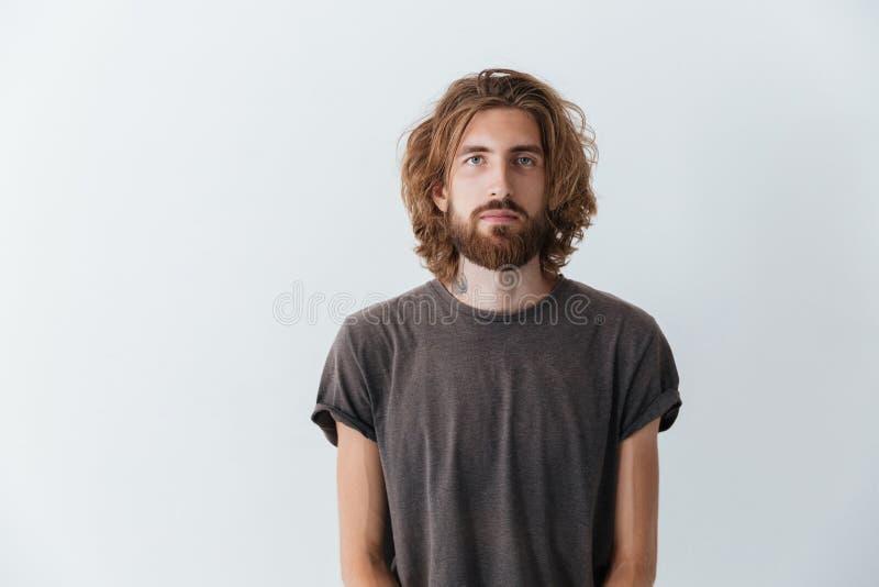 Caucasian stiligt ungt skäggigt isolerat mananseende royaltyfri bild