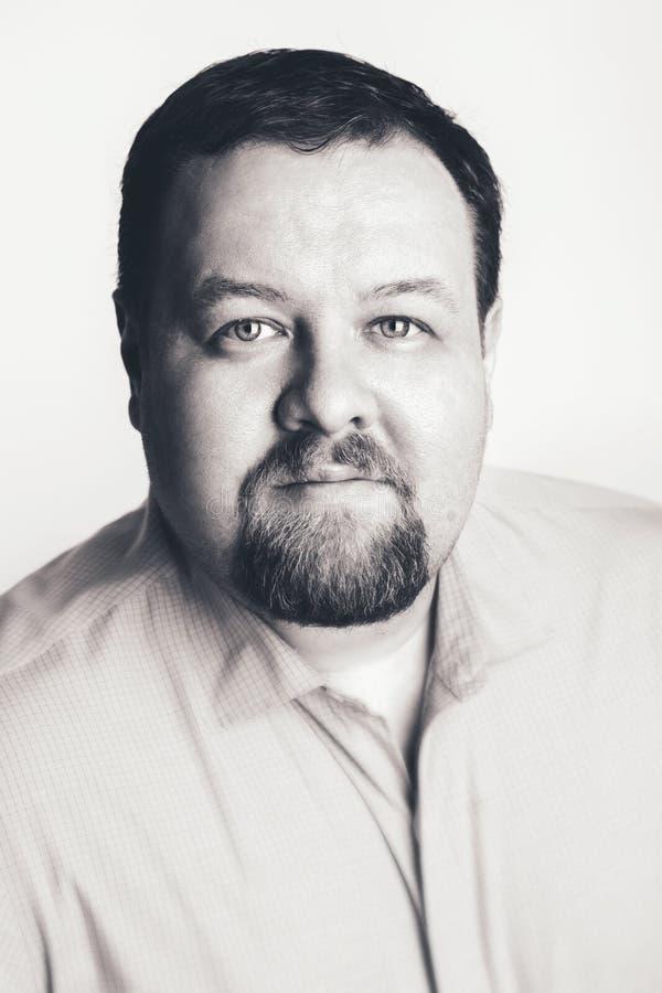 Caucasian stor fet kraftig affärsman med blåa ögon som direkt in camera ser i studio på ljus bakgrund fotografering för bildbyråer