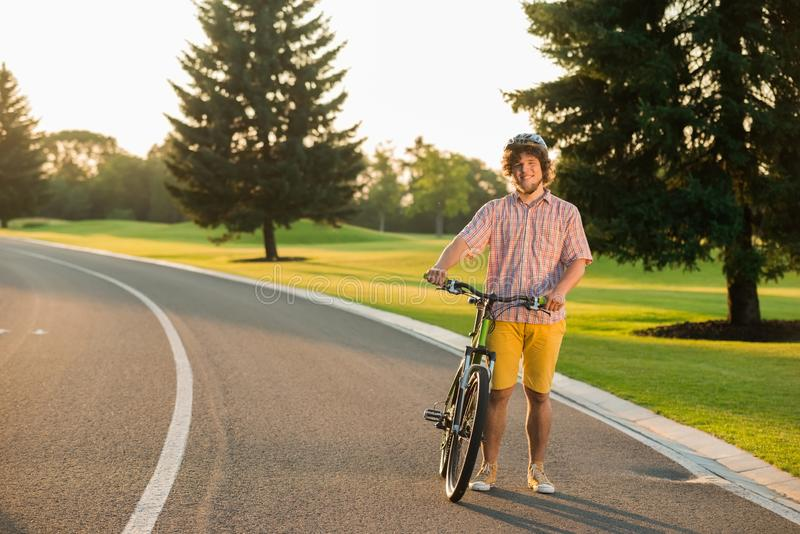 Caucasian student with bicycle outdoors. Happy smiling young biker resting with bike on country road. Summer trip by bike royalty free stock image