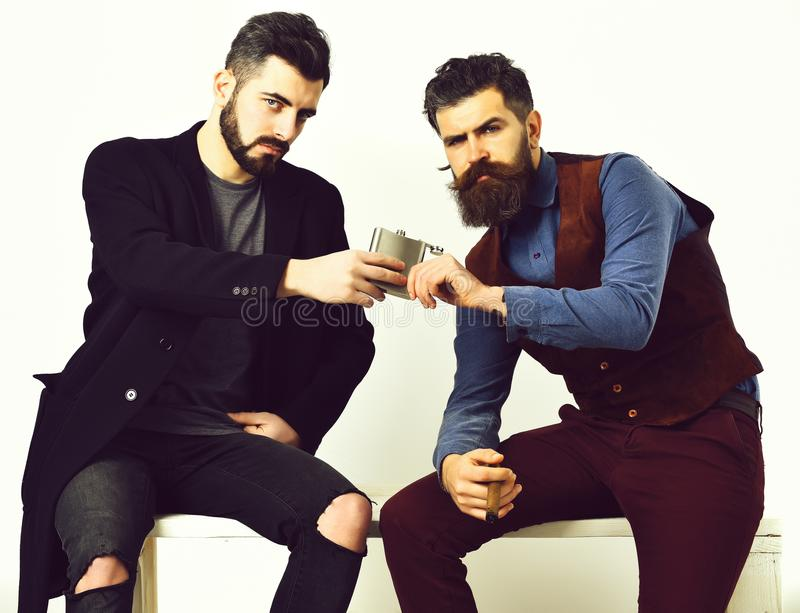 Caucasian stylish hipsters with moustache, holding flask with alcohol drink and cigar isolated on white background. Two. Bearded mens, short and long beard stock photography