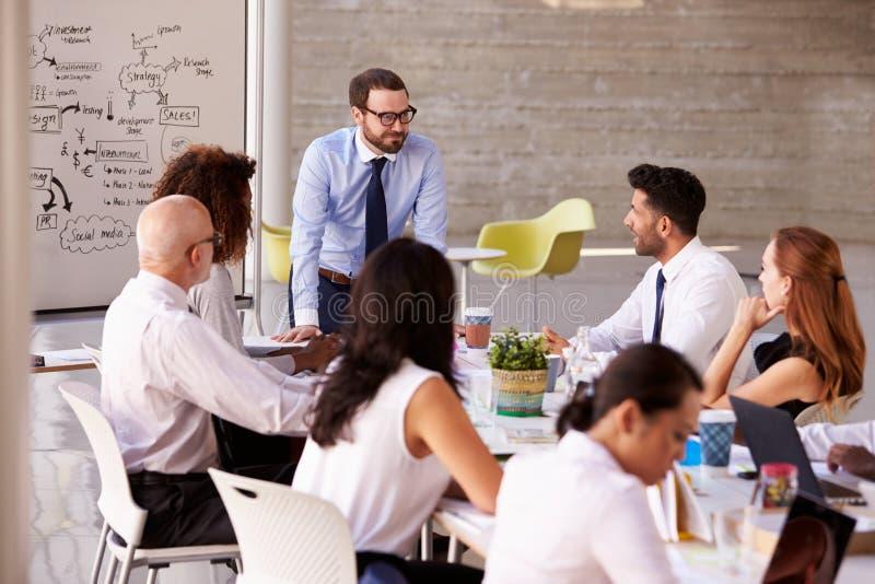 Caucasian tabell för affärsmanLeading Meeting At styrelse royaltyfria bilder