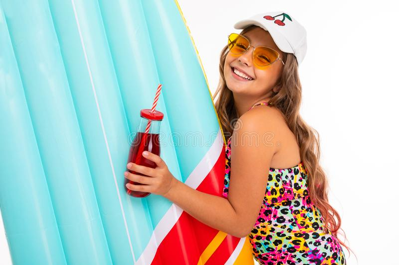 Caucasian tanned girl with a glass of drink and an air mattress for swimming on a white background stock photography