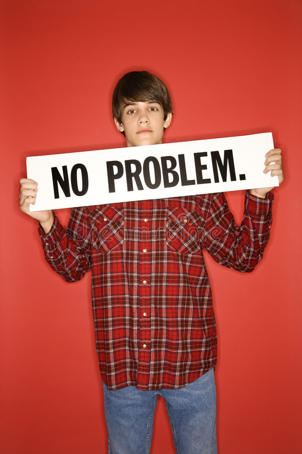 Caucasian teen boy holding no problem sign. Portrait of Caucasian teen boy holding no problem sign under his chin royalty free stock photography