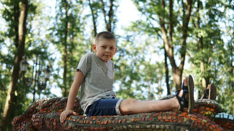 Caucasian teen boy on mosaic bedding. Funny cute teenager in summer park. Portrait of caucasian teen boy on mosaic bedding. Funny cute teenager in summer park at royalty free stock photography