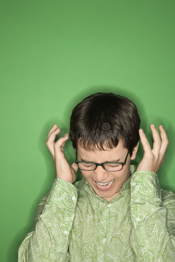 Caucasian teen boy screaming. Portrait of Caucasian teen boy screaming with hands beside ears in front of green background royalty free stock photo