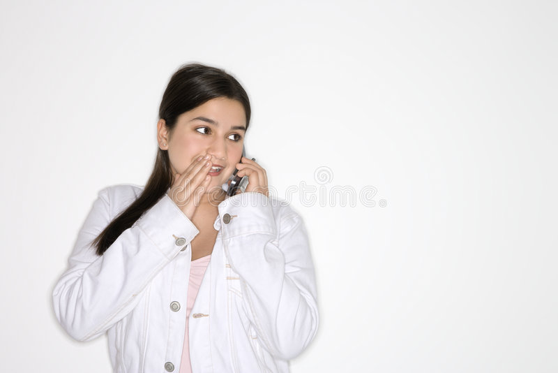 Caucasian teen girl whispering to cellphone. royalty free stock photos