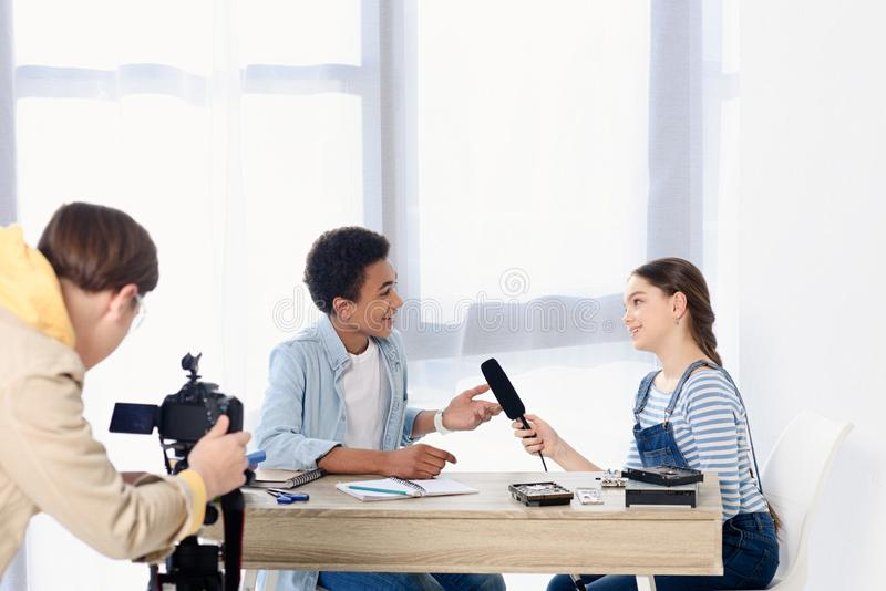 Caucasian teen kid conducting interview with african american friend. For video blog stock photos