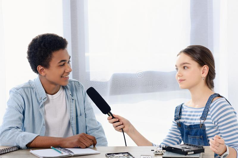 Caucasian teen kid conducting interview with african american friend for vlog. At home royalty free stock photos