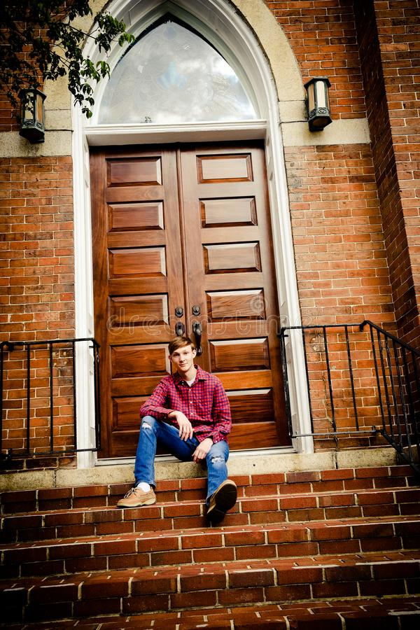 American Teenage Boy Sitting on Steps In Front of Church. Caucasian teenage boy posed in front of a large, wooden church door stock image