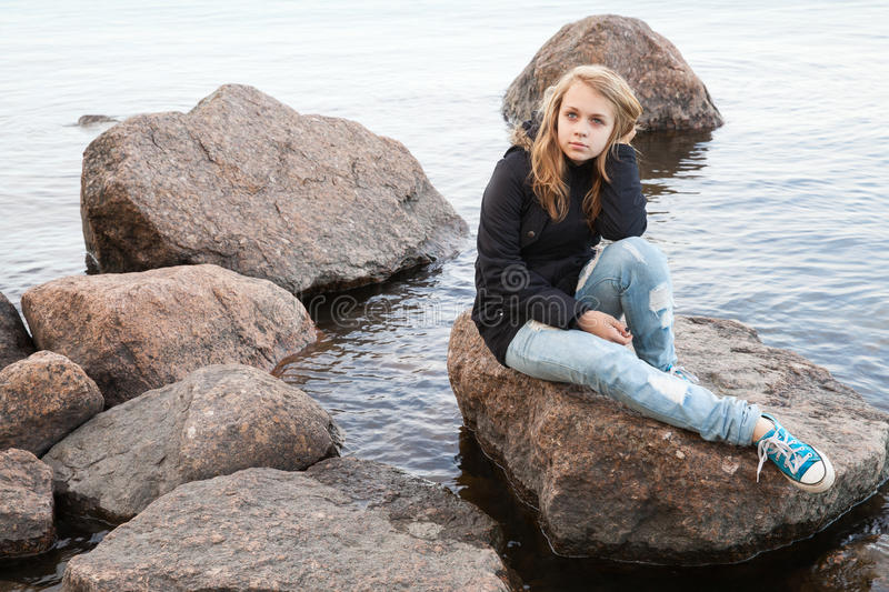 Caucasian teenage girl sitting on coastal stones stock photos
