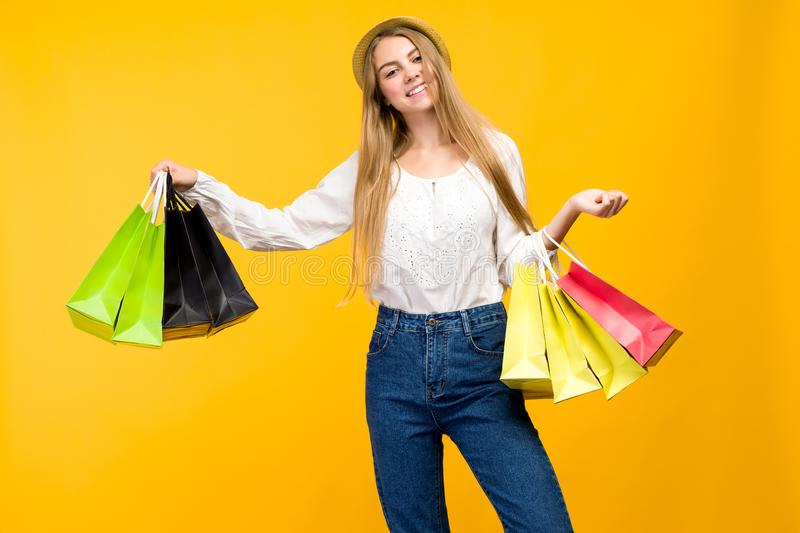 Caucasian teenage girl on yellow background. Stylish young woman with shopping bags in hands stock photo