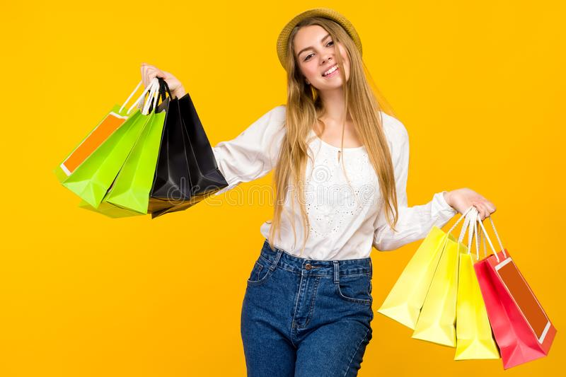 Caucasian teenage girl on yellow background. Stylish young woman with shopping bags in hands royalty free stock photo