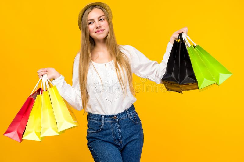 Caucasian teenage girl on yellow background. Stylish young woman with shopping bags in hands. Image, happy, holding, sale, friday, black, people, fashion stock image
