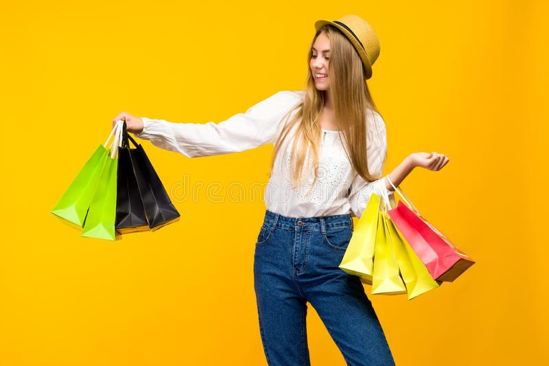 Caucasian teenage girl on yellow background. Stylish young woman with shopping bags in hands royalty free stock image
