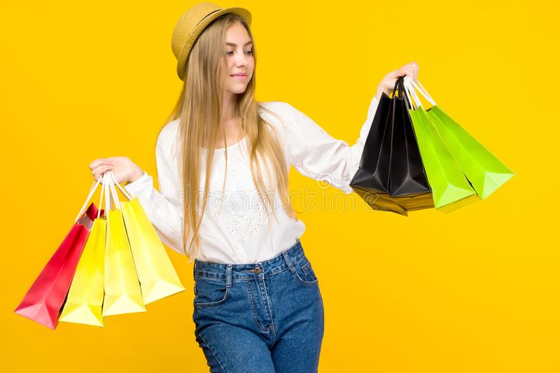 Caucasian teenage girl on yellow background. Stylish young woman with shopping bags in hands stock photography